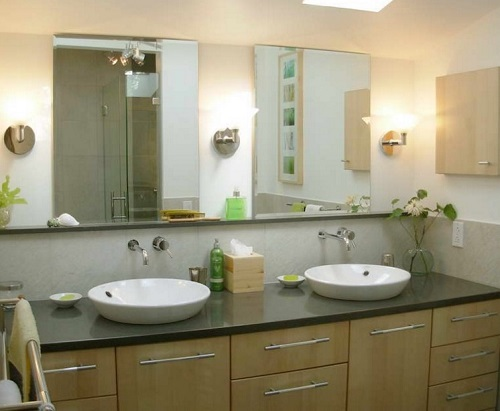 Pair of lights on both sides of mirror in bathroom.