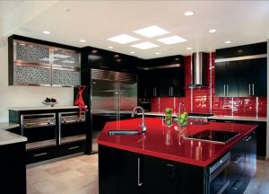 Red kitchen design with black cabinets and red countertops in home kitchen.